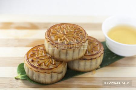 堆叠的月饼、茶在竹叶平铺的背景上