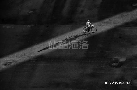 马路上光影中骑车的老人