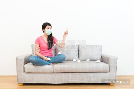 美丽的甜美女人戴着医用口罩 坐在在木地板沙发沙发上 指着白色背景想着生病的解决方案。