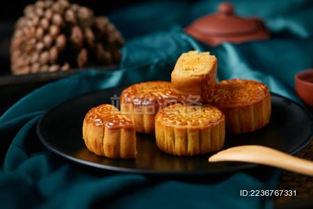 墨绿色丝绸布上的中秋月饼与茶壶