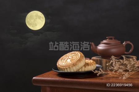 深色背景前摆放在红木桌面上的月饼