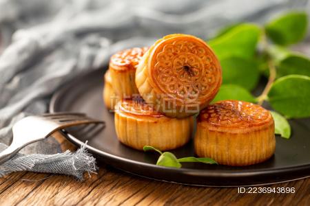满满一盘月饼的一角放在木质背景板上