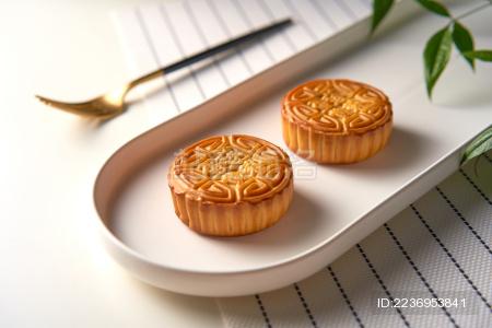 桌面上有两块中式月饼和一把叉子