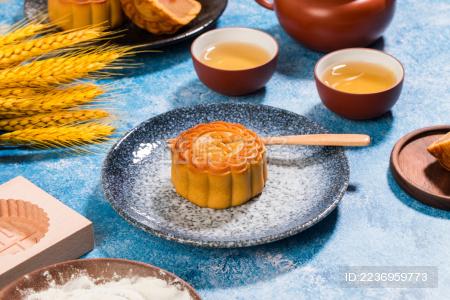 放在盘子里的一个中式流心月饼 周围摆这茶杯和食材