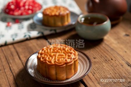 古旧木纹桌子上摆放着月饼和茶壶还有石榴