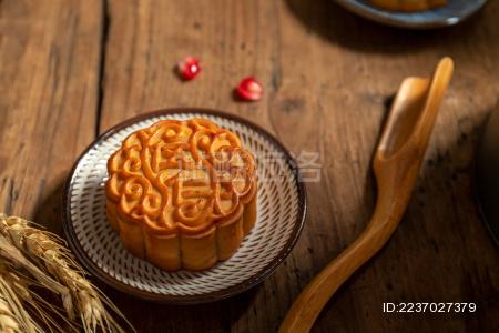 古旧木纹桌子上摆放着月饼和石榴