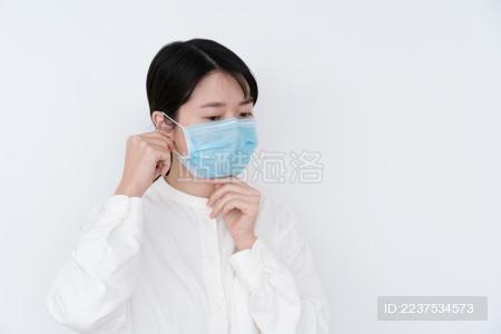 女生在调整口罩的位置