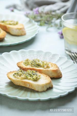 绿色餐桌上绿色盘子上的烤面包片