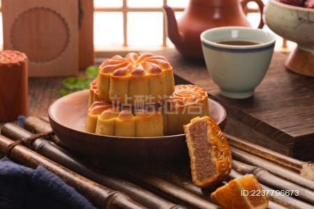 复古背景下装在木盘中的传统中秋小吃月饼
