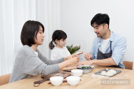 年轻的亚洲爸爸妈妈正在和女儿一起包饺子