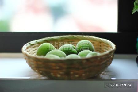 窗台上放在竹编小筐中的绿色青梅