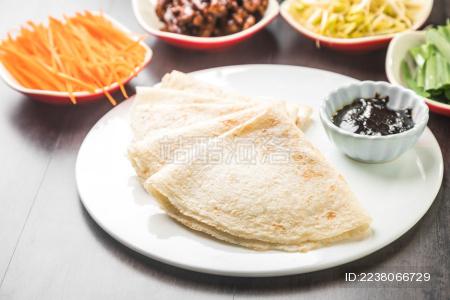 暗色木纹桌面上放着一些卷饼和小菜