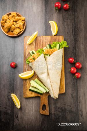 暗色木纹桌面上放着一些墨西哥鸡卷饼和小菜