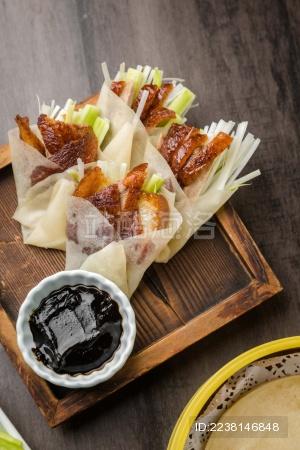 暗色木纹桌上放着一盘卷好肉的春饼