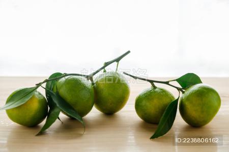 木桌子上随意摆放的新鲜蜜柑