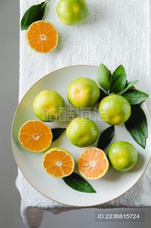 白色桌布上水果盘中的新鲜蜜柑