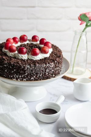 白色调的背景里放着一盘巧克力生日蛋糕