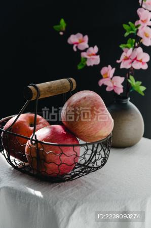 白色桌子上放着一小篮子苹果