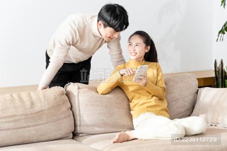 年轻情侣居家使用手机场景