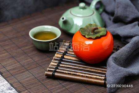 柿子形状的茶叶罐和茶具放在竹垫上