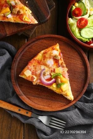 披萨饼放在木盘里和蔬菜沙拉